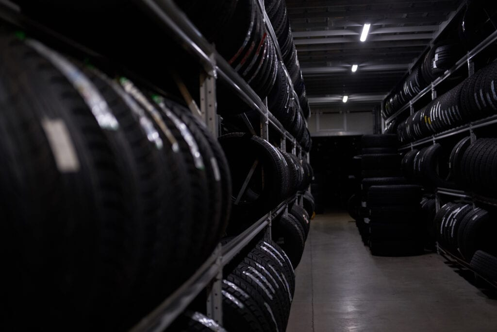 Dark storage full or big variety of new tires at busy storage warehouse.